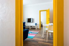 MINSK, BELARUS - March, 2019: retro bright interior of hipster flat apartments with blue sofa, yellow door and colored carpet royalty free stock photography
