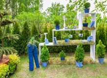 Minsk, Belarus, 23-May-2015: Garden design. Minsk, Belarus, 23-May-2015: Garden composition -  bookshelf with books and potted plants, figure from jeans on Stock Photo
