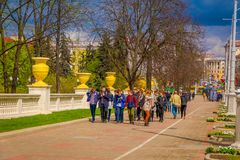 MINSK, BELARUS - MAY 01, 2018: Outdoor view of teenagers walking in the sidewalk in dowtown of the city, close to the. Victory Park in Minsk, Belarus Royalty Free Stock Photography