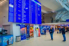 MINSK, BELARUS - MAY 01 2018: Unidentified people walking under a huge departure screen with arrivals and schedule. Inside of the international Minsk airport in Stock Photography