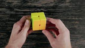 Minsk, Belarus - NOVEMBER 20, 2017: Boys hands solving Rubik`s Cube. Top view stock video