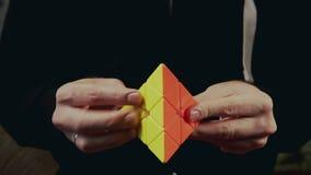 Minsk, Belarus - NOVEMBER 20, 2017: Boys hands solving Rubik`s Pyraminx stock video footage