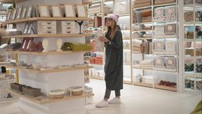 MINSK, BELARUS - OCTOBER 10, 2017. Inside Zara Home retail store in Minsk. A young hipster woman chooses home acessories stock video footage