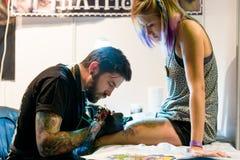 MINSK, BELARUS - SEPTEMBER 19, 2015: Professional artist doing tattoo on client leg Royalty Free Stock Photos