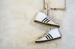 White Adidas Sneakers Hang on Laces. Minsk, Belarus - September 29, 2017: White Adidas Sneakers Hang on Laces and Dry on a Russian Stove, Close-up Royalty Free Stock Images