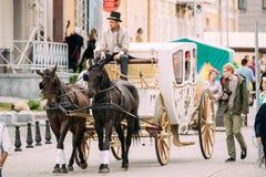 Minsk, Belarus Transporte do feriado tirado por dois cavalos, controlados Foto de Stock Royalty Free