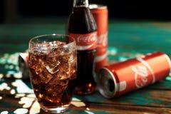 MINSK, BIÉLORUSSIE 25 AOÛT 2016 Peut et un verre de Coca-Cola glacé sur une table en bois Image stock