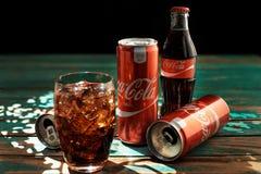 MINSK, BIÉLORUSSIE 25 AOÛT 2016 Peut et un verre de Coca-Cola glacé sur une table en bois Image libre de droits