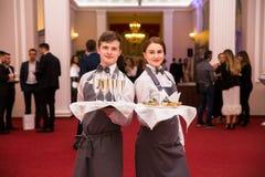 Minsk Białoruś, Czerwiec, - 7, 2018 Kelnery facet i dziewczyna z tacą szkła w ich rękach - fotografia royalty free
