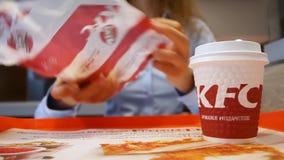 Minsk Białoruś, Lipiec, - 21, 2018: W KFC restauracji, kobieta używa smartphone i je W górę filiżanki z KFC sandw i logo zbiory