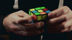 Minsk Białoruś, LISTOPAD, - 20, 2017: Chłopiec wręczają rozwiązywać Rubik ` s sześcian 3x3x3 zbiory wideo