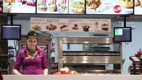 Minsk, Białoruś, Maj 7, 2018: Restauracyjny pracownik zbiera rozkaz i klient otrzymywa rozkaz w KFC restauraci zbiory