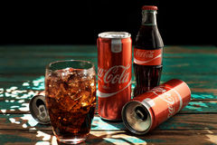 MINSK, BIELORRÚSSIA 25 DE AGOSTO DE 2016 Pode e um vidro de Coca-Cola congelado em uma tabela de madeira imagem de stock royalty free