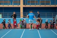 MINSK, BIELORRÚSSIA - 4 DE FEVEREIRO: Childs na bicicleta do equilíbrio do passeio do capacete e na bicicleta corrida durante o t Foto de Stock
