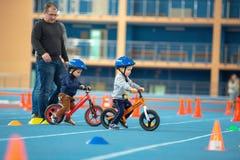 MINSK, BIELORRÚSSIA - 4 DE FEVEREIRO: Childs na bicicleta do equilíbrio do passeio do capacete e na bicicleta corrida durante o t Imagens de Stock