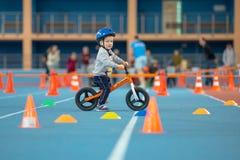 MINSK, BIELORRÚSSIA - 4 DE FEVEREIRO: Childs na bicicleta do equilíbrio do passeio do capacete e na bicicleta corrida durante o t Imagem de Stock Royalty Free