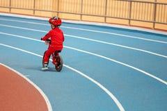 MINSK, BIELORRÚSSIA - 4 DE FEVEREIRO: Childs na bicicleta do equilíbrio do passeio do capacete e na bicicleta corrida durante o t Fotografia de Stock Royalty Free