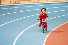 MINSK, BIELORRÚSSIA - 4 DE FEVEREIRO: Childs na bicicleta do equilíbrio do passeio do capacete e na bicicleta corrida durante o t Fotos de Stock Royalty Free
