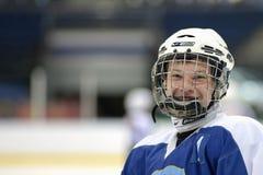 MINSK, BIELORRÚSSIA - 5 DE MAIO DE 2014: Jogador do rapaz pequeno da equipe de hóquei em gelo do ` s das crianças que sorri duran Imagens de Stock