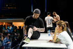 MINSK, BIELORRÚSSIA - 19 DE SETEMBRO DE 2015: Os povos mostram suas tatuagens Imagem de Stock