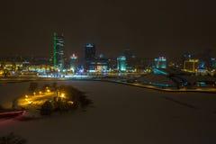 MINSK, BIELORRÚSSIA - EM DEZEMBRO DE 2018: luzes da cidade da noite Arranha-céus claro refletido na água do lago imagem de stock royalty free