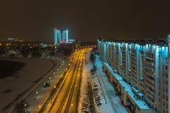MINSK, BIELORRÚSSIA - EM DEZEMBRO DE 2018: luzes da cidade da noite Arranha-céus claro refletido na água do lago foto de stock