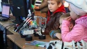 Minsk, Bielorrússia - em maio de 2017: os relógios de um menino como um robô recolhem um cubo do ` s do rubik vídeos de arquivo