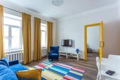 MINSK, BIELORRÚSSIA - em março de 2019: interior brilhante retro de apartamentos lisos do moderno com sofá azul, a porta amarela  foto de stock royalty free