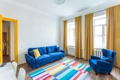 MINSK, BIELORRÚSSIA - em março de 2019: interior brilhante retro de apartamentos lisos do moderno com sofá azul, a porta amarela  imagens de stock royalty free
