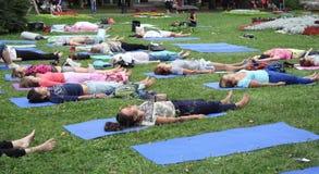 Minsk, Bielorrusia - 16 de agosto de 2014: Yoga practicante de la gente en el parque Imagen de archivo libre de regalías