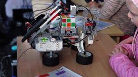 Minsk, Bielorrusia - 13 de mayo de 2017: Robot que soluciona el cubo del ` s de Rubik metrajes