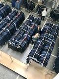 MINSK, BIELORRUSIA, EL 24 DE ABRIL DE 2018; Centro comercial, ropa que cuelga en los estantes Los compradores toman una decisión, Foto de archivo libre de regalías