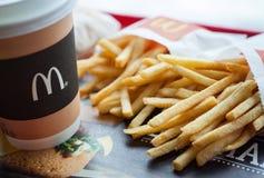 Minsk, Bielorrusia, el 18 de febrero de 2018: Taza de papel de café con el logotipo del ` s de McDonald y de patatas fritas en re Foto de archivo