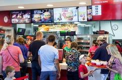 Minsk, Bielorrusia, el 10 de julio de 2017: Restaurante de los alimentos de preparación rápida de KFC Comida de la pedido de la g Fotos de archivo libres de regalías