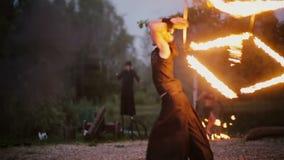 13 06 2015, MINSK, BIELORRUSIA Funcionamiento a solas con el cubo en el fuego Hombre joven que hace el truco peligroso, demostrac almacen de video