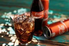 MINSK, BIELORUSSIA 25 AGOSTO 2016 Può e un vetro di Coca-Cola ghiacciato su una tavola di legno Immagine Stock