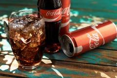 MINSK, BIELORUSSIA 25 AGOSTO 2016 Può e un vetro di Coca-Cola ghiacciato su una tavola di legno Immagini Stock Libere da Diritti