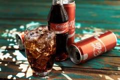 MINSK, BIELORUSSIA 25 AGOSTO 2016 Può e un vetro di Coca-Cola ghiacciato su una tavola di legno Fotografia Stock Libera da Diritti