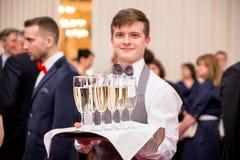 Minsk, Bielorussia - 7 giugno 2018 Il cameriere offre il champagne a Gu fotografie stock libere da diritti