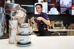 Minsk, Bielorussia, il 24 aprile 2018: Composizione delle tazze e dei chicchi di caffè su fondo di un barista che produce caffè i Fotografie Stock