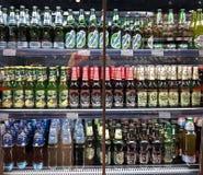 Minsk, Bielorussia, il 12 luglio 2018: Molte bottiglie della birra delle marche differenti mostrano su uno scaffale da vendere in fotografie stock