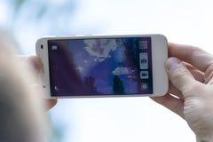 Minsk, Bielorussia, July/08/2017: Un uomo prende le immagini del cielo sul telefono Immagini Stock Libere da Diritti