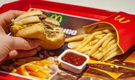 Minsk, Bielorussia, l'8 gennaio 2018: L'uomo sta mangiando al ristorante del ` s di McDonald Fotografie Stock