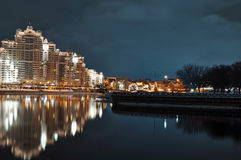 Minsk city nightly landscape with reflection in Svislach river in the evening. Night scene of Trinity hill, downtown Nemiga, Nyami. Nightly landscape of Stock Image