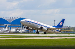 Minsk, Minsk National Airport, Belarus - May 06, 2016: Boeing 73. 7-300 EW-407PA Belavia Airlines taking off with background of blue hangar Royalty Free Stock Photos