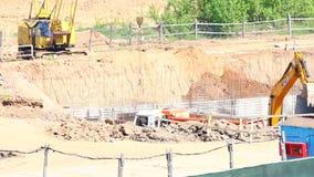 MINSK, MINSKAYA, LE 4 MAI 2018 ; Travail sur le chantier de construction Travaille une grue et une excavatrice de chenille banque de vidéos