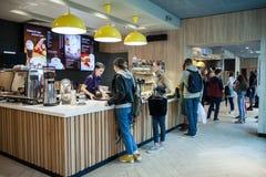 Minsk Vitryssland, April 24, 2018: Inre av McCafe i restaurang för McDonald ` s Bartendern ger beställning till kunden Royaltyfri Fotografi