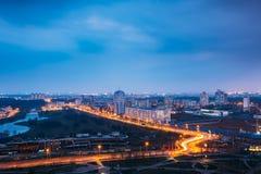 Minsk, Vitryssland Flyg- Cityscape i ljus blå timmeafton och gulingbelysningvår Arkivfoto