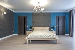 MINSK VITRYSSLAND - Januari, 2019: träsäng i inre av det moderna sovrummet i vindlägenhet i dyra lägenheter royaltyfri bild