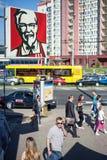 Minsk Vitryssland, juli 10, 2017: Ett tecken på KFC snabbmatrestaurangen på bakgrunden av folk och transport på gatan Royaltyfria Foton